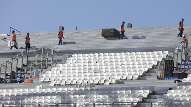 Men work at the Itaquerao, the stadium that will host the World Cup opener in less than three months in Sao Paulo, Brazil, Saturday, March 15, 2014. The Itaquerao was one of the six stadiums that were supposed to be finished by the end of 2013, but a crane collapse that killed two workers in November caused significant delays to the venue where Brazil will play Croatia on June 12. The stadium is not expected to be ready before mid-April