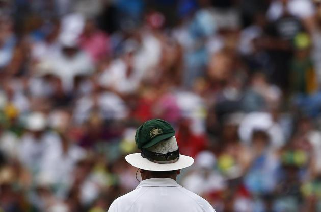Australia's Lyon's cap is seen on the umpire's hat as he bowls during the fourth day of the second Ashes test cricket match against England in Adelaide