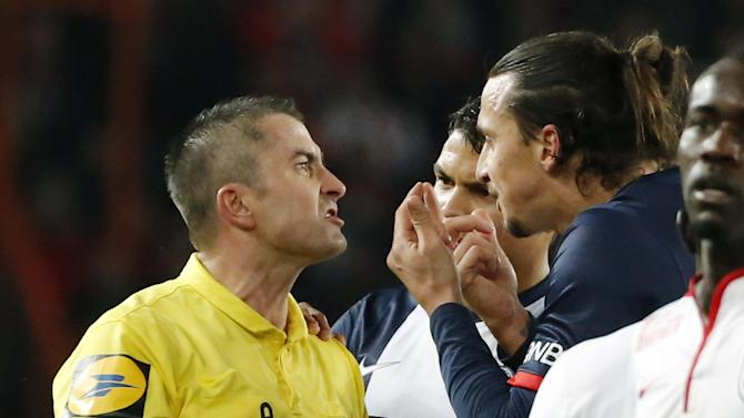 Referee Fredy Gautrel, left, argues with Paris-Saint-Germain's Zlatan Ibrahimovic of Sweden, right, after he was booked during a French league one soccer match between Paris-Saint-Germain and Lille at Parc des Princes stadium in Paris, Sunday Dec. 22, 2013.  Ibrahimovic and Lille's Antonio Mavuba were booked for shoving each other