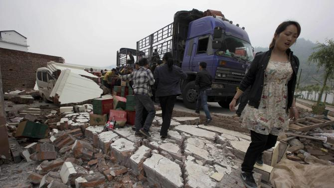 A woman walks past a truck distributing water near a wall that collapsed onto a vehicle after an earthquake struck the county seat of Lushan in southwestern China's Sichuan province, Monday, April 22, 2013. Saturday's earthquake in Sichuan province killed at least 186 people, injured more than 11,000 and left nearly two dozen missing, mostly in the rural communities around Ya'an city, along the same seismic fault where a devastating quake to the north killed more than 90,000 people in Sichuan and neighboring areas five years ago in one of China's worst natural disasters. (AP Photo/Ng Han Guan)
