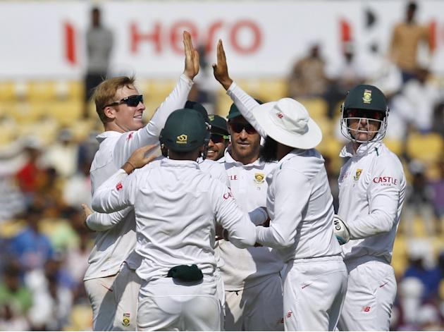 South Africa's Harmer celebrates with his teammates after taking the wicket of India's Sharma on the first day of their third test cricket match in Nagpur