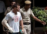 Delhi policemen escort Australian cricketer Luke Pomersbach (C) before a court appearance in New Delhi. Indian police on Friday arrested and charged Pomersbach with molesting a woman and badly beating up her fiance after a late-night party at a posh New Delhi hotel