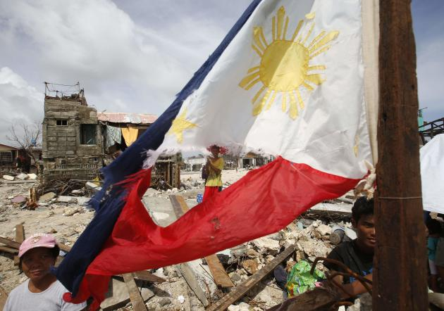 Typhoon victims wait for relief supplies near a tattered Philippine flag in Hernani, Samar, that was hit by super Typhoon Haiyan in central Philippines November 11, 2013. Dazed survivors of super Typhoon Haiyan that swept through the central Philippines killing an estimated 10,000 people begged for help and scavenged for food, water and medicine on Monday, threatening to overwhelm military and rescue resources. REUTERS/Erik De Castro (PHILIPPINES - Tags: DISASTER ENVIRONMENT)