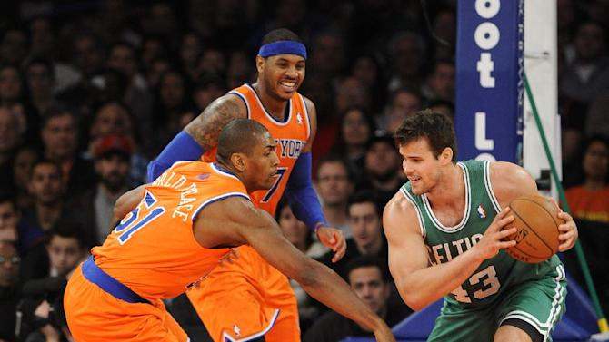 Boston Celtics' Kris Humphries (43) keeps the ball away from New York Knicks' Metta World Peace (51) and Carmelo Anthony (7) during the second half an NBA basketball game on Sunday, Dec. 8, 2013, in New York