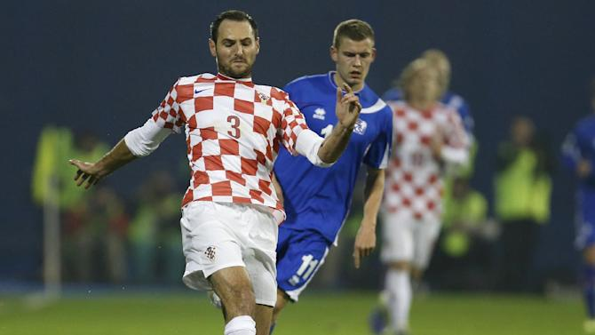 """In this Nov. 19, 2013 file picture Croatia's defender Josip Simunic, left, is challenged by Iceland's Alfred Finnbogason during their World Cup qualifying playoff second leg soccer match against Iceland, in Zagreb, Croatia. Croatia's World Cup qualification celebrations have been marred by apparent pro-Nazi chants by fans and defender Joe Simunic. Croatia qualified for the World Cup with a 2-0 win over Iceland on Tuesday. Video footage shows Simunic taking a microphone to the field after the match and shouting to the fans: """"For the homeland!"""" The fans respond: """"Ready!"""" That was the war call used by the Croatian pro-Nazi puppet regime that ruled the state during World War II when tens of thousands Jews, Serbs and others perished in concentration camps. The Australian-born Simunic defended his action, saying """"some people have to learn some history."""""""