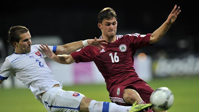 Latvia's Valerijs Sabala, right, vies for the ball with Slovakia's Peter Pekarik during a World Cup 2014 Group G qualification match in Riga, Latvia, on Tuesday. Oct.15, 2013