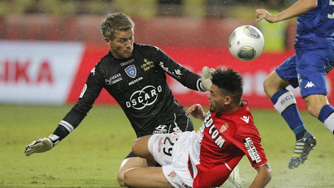 Monaco's Emmanuel Riviere of France, right, challenges for the ball with Bastia's goalkeeper Mickael Landreau of France during their French League One soccer match, in Monaco stadium, Wednesday, Sept, 25, 2013