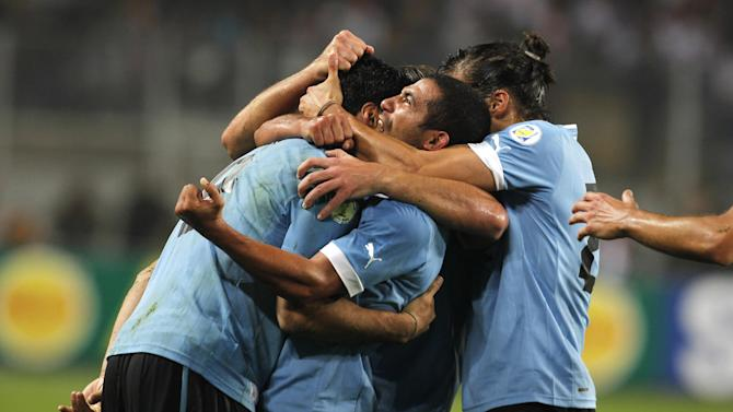 Uruguay's Luis Suarez, left, celebrates with teammates after scoring against Peru at a 2014 World Cup qualifying soccer game in Lima, Peru, Friday, Sept. 6, 2013