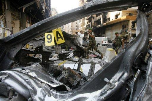 Soldiers walk behind a burnt vehicle as they work on the scene of the previous day's car bomb explosion in southern Beirut on August 16, 2013. The death toll has risen to at least 27, the health ministry said Saturday