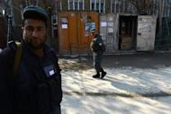 Afghan policemen stand guard at the site where a female police officer shot dead a foreign civilian adviser at police headquarters in Kabul on December 24, 2012. The female Afghan police officer who shot dead a NATO adviser in Kabul is an Iranian national who wanted to kill senior security members, officials said Tuesday