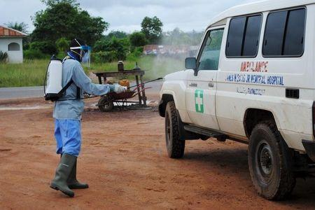A health worker sprays disinfectant on an ambulance in Nedowein