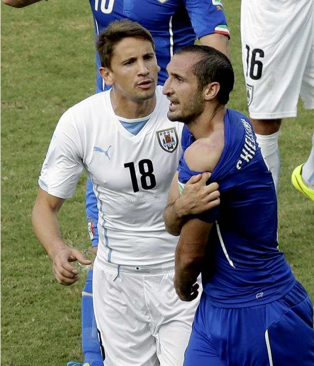 Italy's Giorgio Chiellini, right, shows his shoulder after colliding with Uruguay's Luis Suarez's mouth as Uruguay's Gaston Ramirez (18) watches during the group D World Cup soccer match between Italy