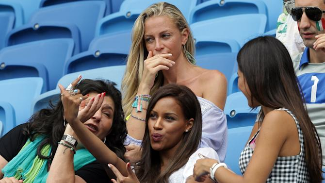 Fanny Neguesha, fiancee of Italy's Mario Balotelli, bottom center, waits for the start of the group D World Cup soccer match between Italy and Uruguay at the Arena das Dunas in Natal, Brazil, Tuesday, June 24, 2014. (AP Photo/Antonio Calanni)
