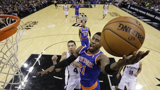 New York Knicks' Iman Shumpert (21) scores in front of San Antonio Spurs' Danny Green (4) during the first half of an NBA basketball game, Thursday, Jan. 2, 2014, in San Antonio. (AP Photo/Eric Gay)