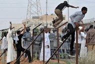Sudanese protesters climb over a fence outside the US embassy in Khartoum on September 14 during a protest against an amateur film mocking Islam. Furious protesters targeted symbols of US influence in cities across the Muslim world on Friday, attacking embassies, schools and restaurants in retaliation for a film that mocks Islam