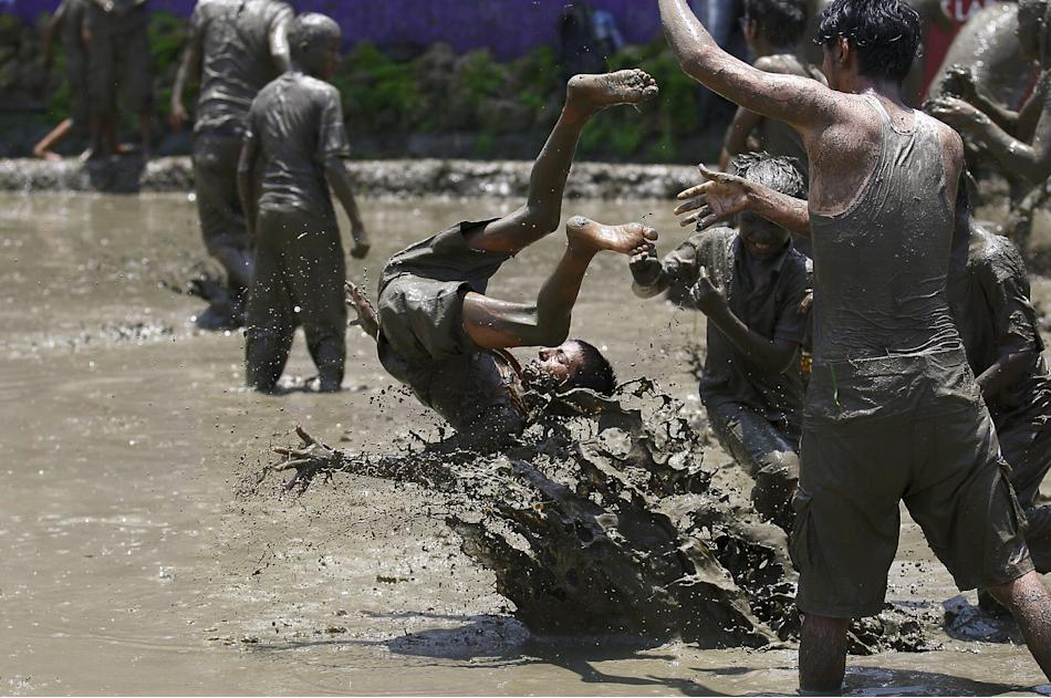 A boy is tossed on the mud during the Asar Pandhra festival in Pokhara