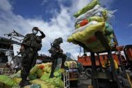 Filipino soldiers take part in a relief operation for victims of Typhoon Haiyan, at Tacloban airport November 16, 2013. Survivors began rebuilding homes destroyed by Haiyan, one of the world's most powerful typhoons, and emergency supplies flowed into ravaged Philippine islands, as the United Nations more than doubled its estimate of people made homeless to nearly two million. REUTERS/Bobby Yip