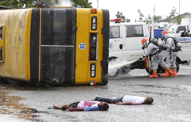 Mock injured passengers lie beside a bus while members of the fire and rescue service, wearing chemical suits, put out a chemical fire during a simulation at the first search and rescue summit in Cebu