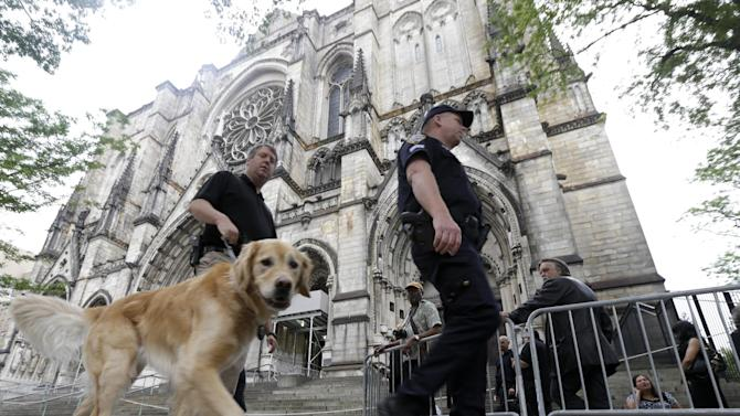"Officials walk with a dog as they secure an area outside of at Cathedral Church of Saint John the Divine, where people gathered behind a barricade, before funeral services for actor James Gandolfini, Thursday, June 27, 2013, in New York. Gandolfini, who played Tony Soprano in the HBO show ""The Sopranos"", died while vacationing in Italy last week. (AP Photo/Julio Cortez)"