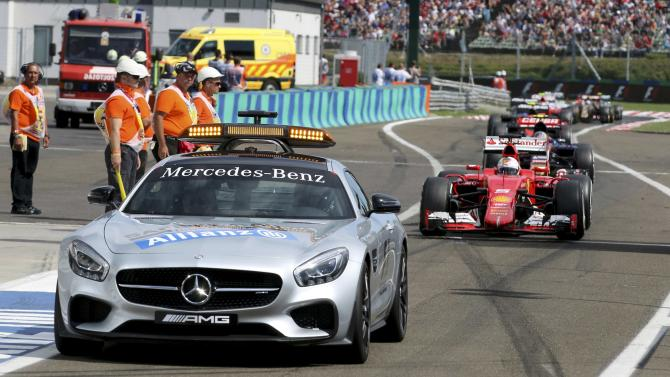 Formula 1 drivers follow a safety car into the pit lane during the Hungarian F1 Grand Prix at the Hungaroring circuit, near Budapest