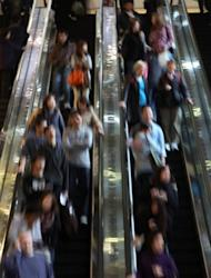 File photo shows people on an escalator in Hong Kong. Younger Hong Kong residents typically live at home deep into their 20s or 30s because they can't afford to marry and move out earlier, meaning that many sleep in close proximity to their parents in cramped apartments