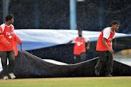 Grounds crews pull out tarps in the second rain delay during the fourth day of the second-of-three Test matches between Australia and West Indies at Queen's Park Oval in Port of Spain, Trinidad. Australia built up a lead of 127 runs over the West Indies on the fourth day of the second Test before heavy rain swamped the Queen's Park Oval and play was abandoned