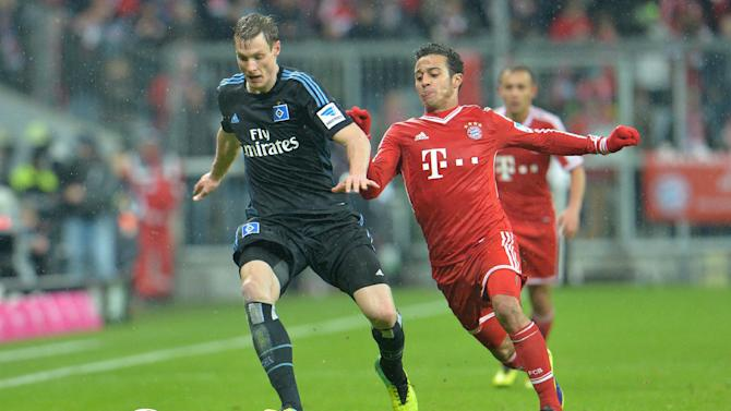 Bayern's Thiago Alcantara of Spain, right, and Hamburg's Marcell Jansen challenge for the ball   during  the German first division Bundesliga soccer match between FC Bayern Munich and Hamburger SV  in Munich, Germany, Saturday, Dec. 14, 2013