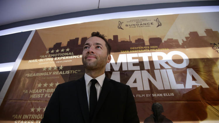 "In this Thursday Oct.3, 2013 photo, Briton Sean Ellis, writer-director of ""Metro Manila"" - Britain's nominee to the Oscar Awards' best foreign language film, poses by his film's poster prior to its premier screening at a cinema in Taguig city, east of Manila, Philippines. (AP Photo/Bullit Marquez)"