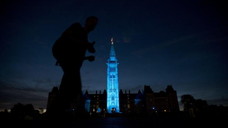 The Peace tower and Parliament buildings in Ottawa, Ontario are illuminated in blue to celebrate the birth of the royal baby on Monday July 22, 2013. (AP Photo/The Canadian Press, Adrian Wyld)