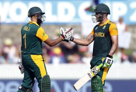 South Africa's Hashim Amla celebrates with team mate Faf du Plessis after reaching his century during the Cricket World Cup match against Ireland at Manuka Oval in Canberra