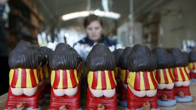 """FC Barcelona's soccer captain Carles Puyol """"caganers"""" figurines are seen in a pottery stall in Torroella de Montgri"""