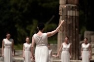 Actress Ino Menegaki, playing the high priestess, holds the Olympic flame during the torch lighting ceremony in ancient Olympia, Greece, on May 10. The ceremony signals the final countdown to the start of this year's summer Games in London