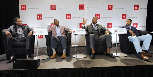 Arizona Cardinals wide receiver Larry Fitzgerald gestures as he answers a question during a panel discussion at Harvard University in Cambridge, Mass., Wednesday, April 23, 2014. Fitzgerald was a feat