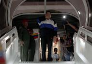 A picture provided by the Venezuelan presidency shows President Hugo Chavez (centre) blowing kisses from the plane stairs just before departing from Caracas to Cuba on December 10