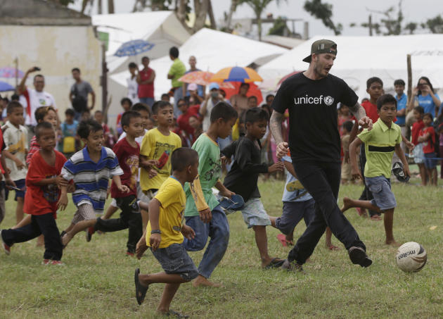 FILE - In this Friday, Feb. 14, 2014 file photo, David Beckham plays soccer with young typhoon-survivors during his visit to typhoon-ravaged Tanauan township, Leyte province in central Philippines.