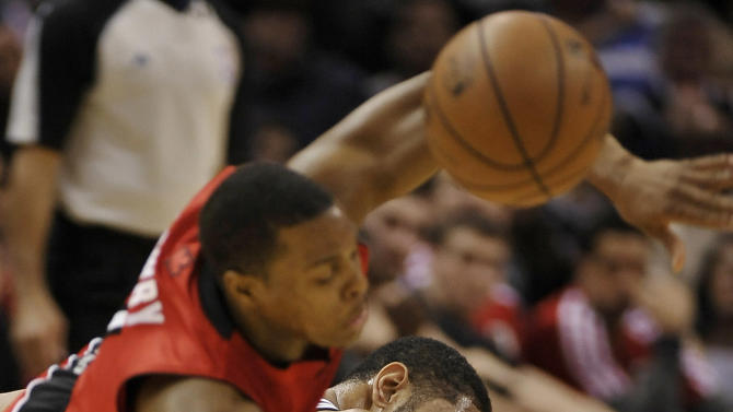 San Antonio Spurs power forward Tim Duncan, right, chases a loose ball against Toronto Raptors guard Kyle Lowry during the first half of an NBA basketball game on Monday, Dec. 23, 2013, in San Antonio
