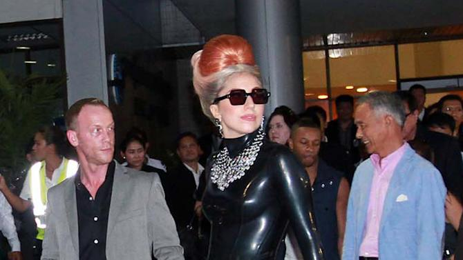 U.S. singer Lady Gaga pauses while making her way to a waiting car upon her arrival at Don Muang airport in Bangkok, Thailand Wednesday, May 23, 2012. Lady Gaga is performing a concert in Bangkok on Friday, May 25, 2012.  (AP Photo)
