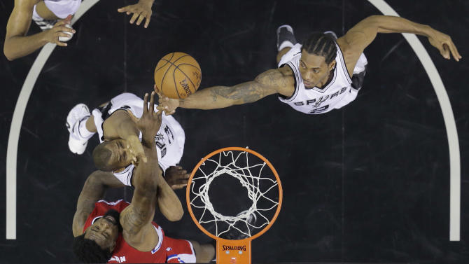 Los Angeles Clippers' DeAndre Jordan, bottom left, goes up for a rebound along with San Antonio Spurs' Boris Diaw, left, and Kawhi Leonard during the first half of Game 3 in an NBA basketball first-round playoff series, Friday, April 24, 2015, in San Antonio. (AP Photo/Darren Abate)