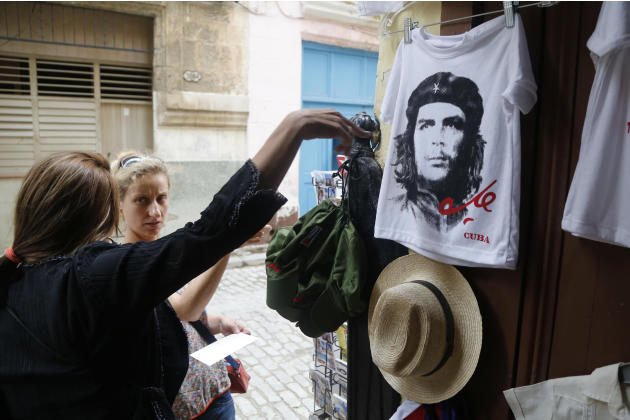 "A vendor sells Ernesto ""Che"" Guevara T-shirts and other souvenirs in Old Havana, Cuba, Monday, June 1, 2015. Travel experts and upscale magazines are urging travel to Cuba before it changes."