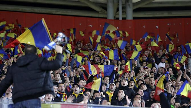 Romanian fans wave their country's flag before a World Cup qualifying playoff first leg soccer match between Greece and Romania at the Karaiskaki stadium in the port of Piraeus, near Athens, Friday, Nov. 15, 2013