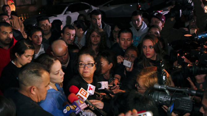 Rosie Rivera, sister of singer Jenni Rivera, hugs their mother Rosa Rivera, as Pastor Pedro Rivera Jr., left, watches during a news conference with friends and family outside the home of Rivera's father in Lakewood, Calif., on Sunday, Dec. 9, 2012. Authorities have not confirmed her death, but Rivera's relatives in the U.S. say they have few doubts that she was on the Learjet 25 that disintegrated on impact Sunday in rugged territory in Nuevo Leon state in northern Mexico. (AP Photo/Patrick T. Fallon)