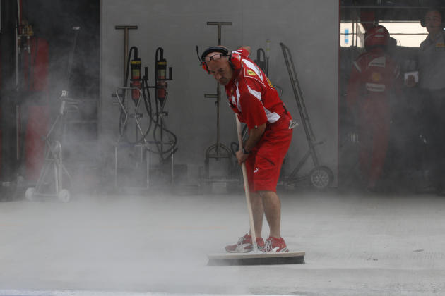 A Ferrari crew sweeps their pit during Indian Formula One Grand Prix at the Buddh International Circuit in Noida, 38 kilometers (24 miles) from New Delhi, India Sunday, Oct. 30, 2011. (AP Photo/Eugene