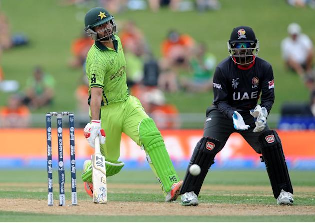 Pakistan batsman Ahmad Shahzad, left, runs to make his ground as United Arab Emirates wicketkeeper Swapnil Patil waits for the ball during their Cricket World Cup Pool B match in Napier, New Zealand,