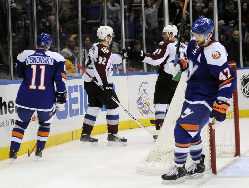 Colorado Avalanche's Gabriel Landeskog (92) celebrates his empty net goal with Jamie McGinn, second from right, as New York Islanders' Lubomir Visnovsky, left, and Andrew MacDonald (47) skate
