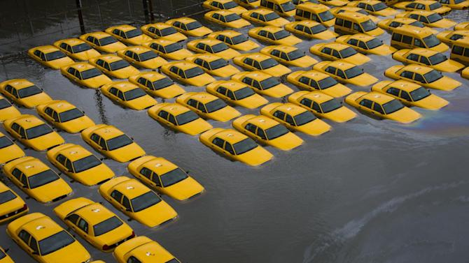FILE - In this Oct. 30, 2012 file photo, a parking lot full of yellow cabs is flooded as a result of Superstorm Sandy in Hoboken, N.J. Sandy damaged or destroyed several homes and businesses, more than 72,000 in New Jersey alone, according to Gov. Chris Christie. (AP Photo/Charles Sykes, File)