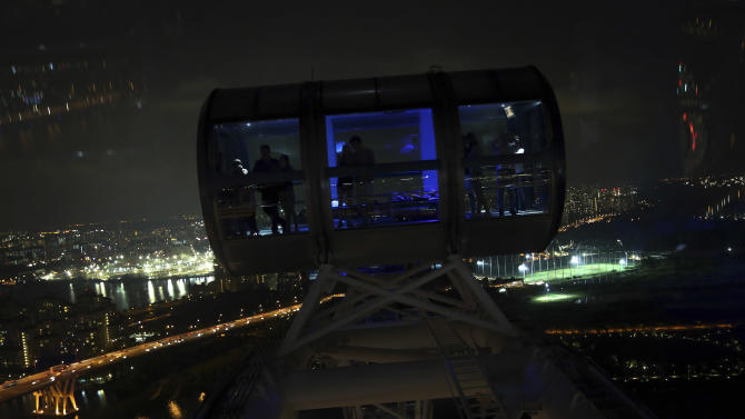 People ride in darkness in a capsule of the Singapore Flyer as the lights are switched off for a whole hour on Saturday, March 23, 2013 in Singapore. More than 100 buildings, locations and organizations in Singapore switched off their lights as part of the global Earth Hour initiative by World Wide Fund for Nature (WWF) along with other national monuments around the world. (AP Photo/Wong Maye-E)