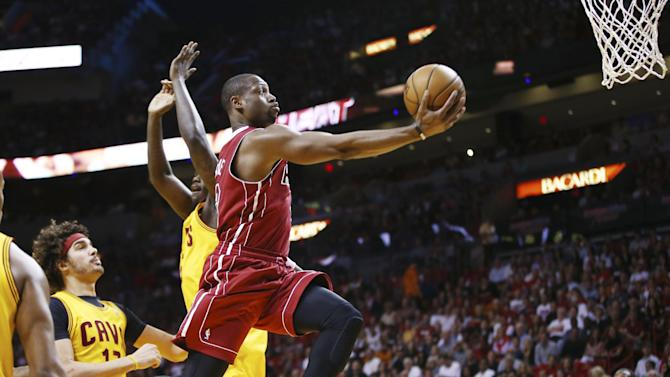 Miami Heat's Dwyane Wade (3) slides past Cleveland Cavaliers' Anthony Bennett (15) and Anderson Varejao (17) for two points during the first half of an NBA basketball game in Miami, Saturday, Dec. 14, 2013