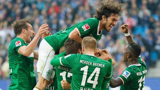 Bremen's players with Santiago Garcia at the top of the huddle celebrate the  opening goal during the Bundesliga soccer match between Hamburger SV and Werder Bremen a  in Hamburg, Germany, Saturday Sept. 21, 2013
