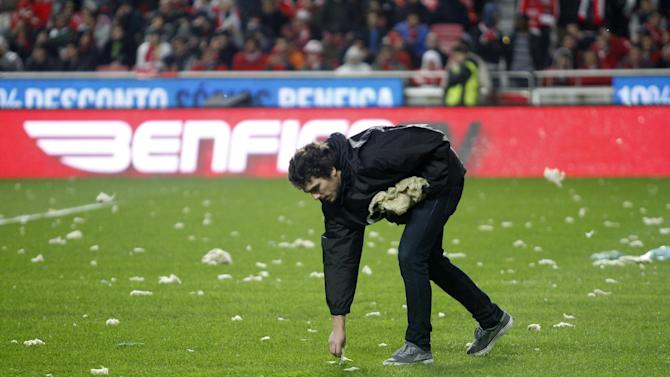An assistant removes pieces of debris fallen from the roof, prior the Portuguese league soccer match between Benfica and Sporting at Benfica's Luz stadium, in Lisbon, Sunday, Feb. 9, 2014. Strong winds damaged the stadium roof before kick off and debris fell on the pitch and stands. It was decided the match should be postponed for security reasons