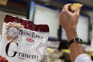 A man eats a Barilla's snack as he works in his office in Rome September 27, 2013. REUTERS/Tony Gentile
